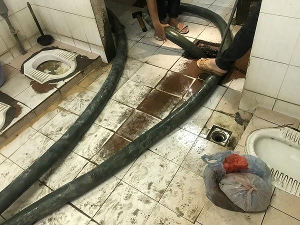 Nhân viên tiến hành luồn ống hút xuống hầm để hút chất thải ra ngoài