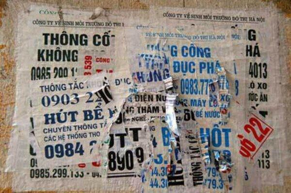 Những tờ quảng cáo được dán chằng chịt trên tường và cột điện